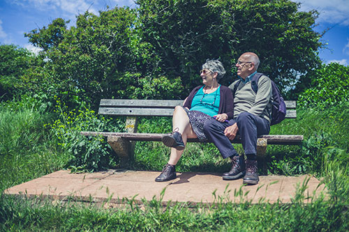 Senior couple relaxing on a bench in the courtyside